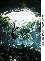Descending in Cenote - A young woman free dives (breath hold...