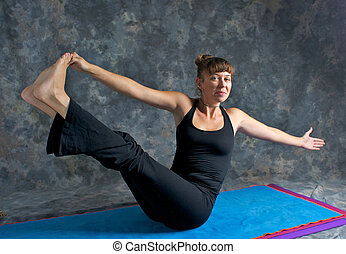 A brown haired caucasian woman is smiling doing yoga exercise, Navasana Pose or Rotated Boat posture  on yoga mat in studio with mottled background.