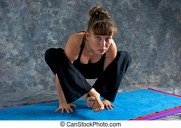 A brown haired caucasian woman is doing advanced asana yoga exercise, Tittibhasana Pose or Firefly  posture on yoga mat in studio with mottled background.