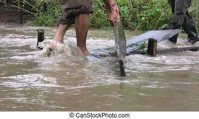 Repairing A Washed Out Foot Bridge - Two men work hard to...