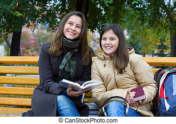 Two young girls reading a the park
