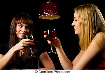 Two young women in a bar - Two young women drinking red wine...