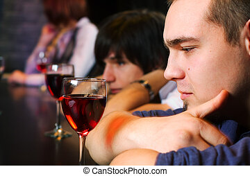Young men relaxing in a bar - Young men drinking red wine on...