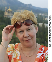 Mature woman straightens sunglasses - Portrait of an...