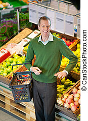 Man in Grocery Store - Mid adult man carrying shopping...