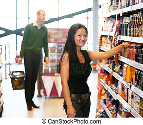 Portrait of a woman in grocery store - Smiling woman looking...
