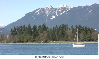 Sailboat - A sailboat passes in front of a majestic mountain...