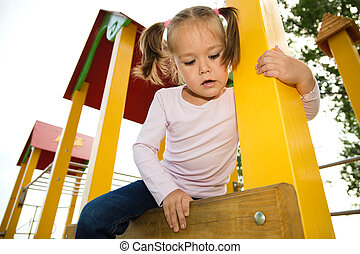 Little girl is playing in playground