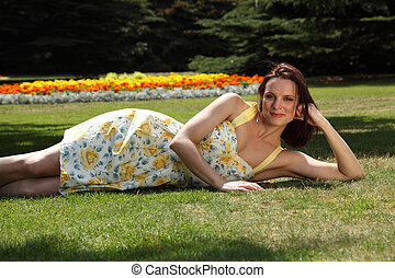 Sexy young woman lying on grass in summer sunshine - Lovely...