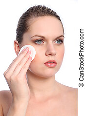 Beautiful girl using cosmetics cotton pad on face -...