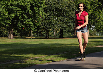 Sexy young woman roller skating in park sunshine - Fit...