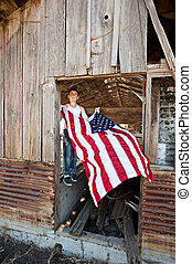 Boy hanging American flag - A patriotic teenager gets ready...