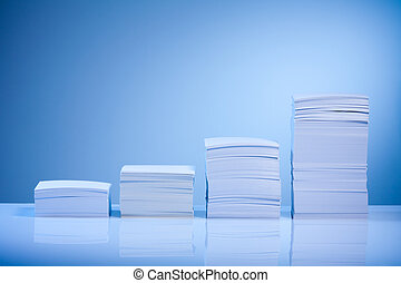 Growth in business represented by paper piles incrementing...