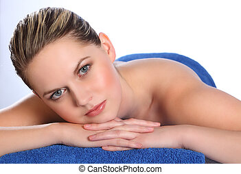 Young woman lying on health spa massage table