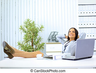 Portrait of pretty young business woman resting at her desk