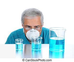 Scientist examining liquid in beakers