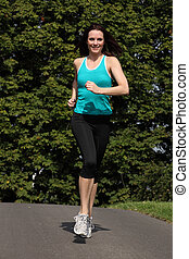Happy fit woman jogging exercise in park sun