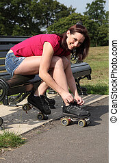 Beautiful girl ties roller skates on park bench - Fun...