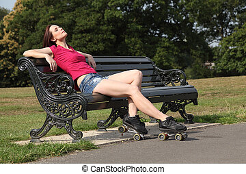 Beautiful roller skater woman sun tans in the park - Sitting...