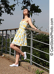 Young woman summer dress enjoys sunshine in park - Happy...