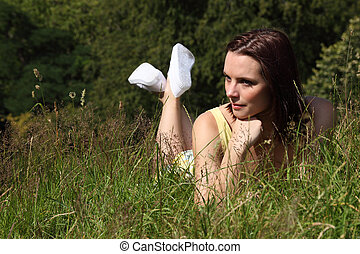 Beautiful young woman lying in countryside grass - Beautiful...