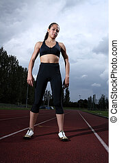 Beautiful fit young woman athlete on running track -...