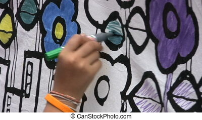 Coloring A Mural - A teenager colors a mural at a school...