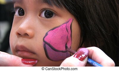 Butterfly Face Painting - A cute little Asian girl waits...