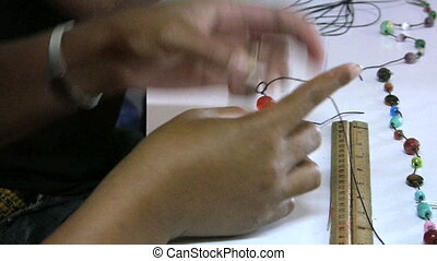 Asian Lady Making A Necklace - An Asian lady makes special...