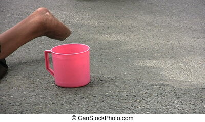 Beggar With A Pink Cup - A handicapped or disabled beggar...