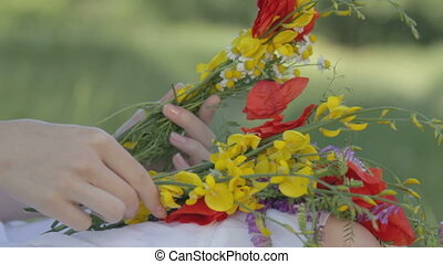 Young woman makes bouquet on nature