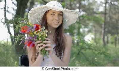 Young woman with bouquet resting on - Young woman in white...