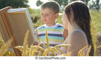 Young woman with little boy drawing