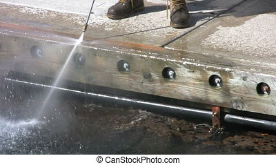 Cleaning The Dock - A worker does spring cleaning on a dock...
