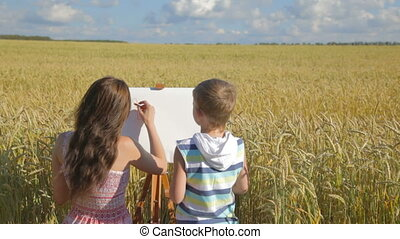 Young woman with boy drawing with c