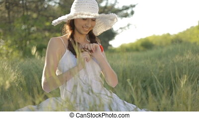 Young woman in white hat resting on - Young woman in white...