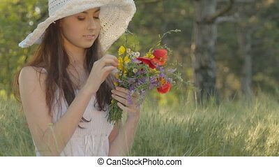 Young woman smelling bouquet of wil - CLIP EDIT Young woman...
