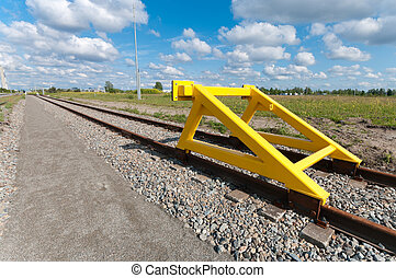 train stop - yellow buffer stop at the end of a railroad...