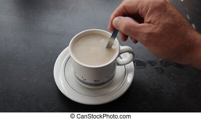 Tea cup being stirred.  - Cup with a teabag being stirred.