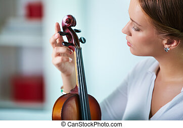 Girl with violin - Portrait of a young female tuning the...
