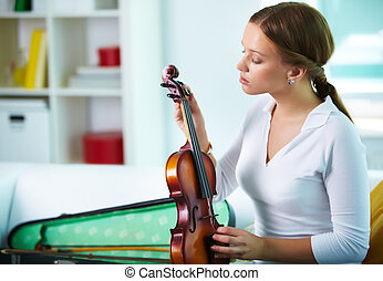 Tuning the violin - Portrait of a young female tuning the...