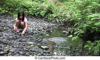 Asian Girl Throws Rocks In Creek - A young Thai girls throw...