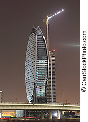 Construction of modern highrise building at night. Dubai, United Arab Emirates