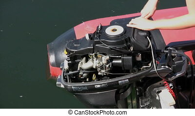 Fixing An Outboard Motor - A woman using a ratchet wrench...