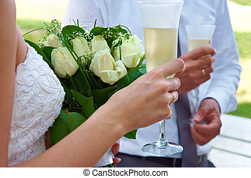 bride and groom holding glasses of celebratory champagne and...