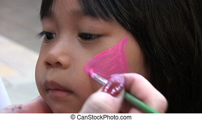 Face Painting Sequence - A cute little Asian girl sits...