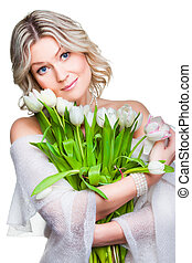 beautiful young blonde woman with blue eyes holding bouquet of spring tulips wearing cozy woolen shawl on isolated white background