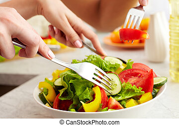 Prepared salad - Close-up of human hands with forks tasting...