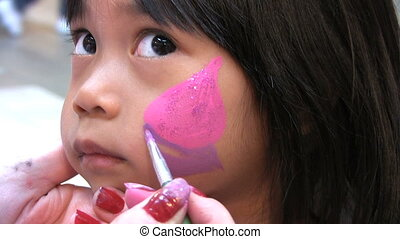 Face Painting Fun - A cute little Asian girl sits patiently...