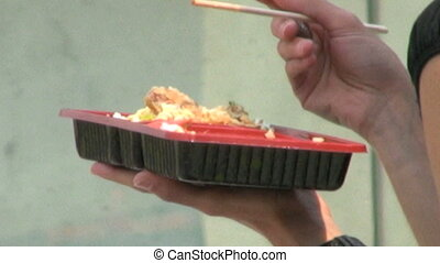 Eating With Chopsticks - A woman eating her lunch with...